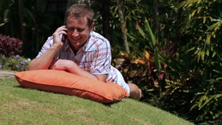 Man sitting in the garden and typing message on smartphone