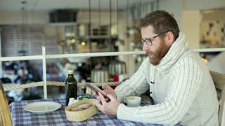 Man sitting in the restaurant and talking on cellphone