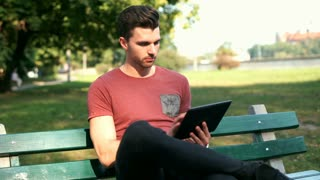 Man sitting on the bench and scrolling something on tablet in the park