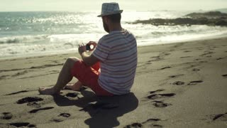 Man sitting on the sandy beach and doing selfie on smartphone, steadycam shot