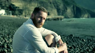Man sitting on the shingle beach and doing serious look to the camera