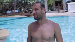 Man smiling to the camera in the swimming pool