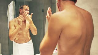 Man spreads cream on his face in the bathroom after shower