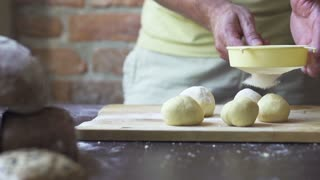 man sprinkling dough with flour, slow motion at 240 fps