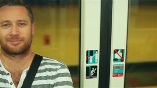 Man standing and smiling to the camera in subway, steadycam shot