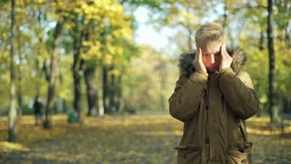 Man standing in the autumnal park and having a headache