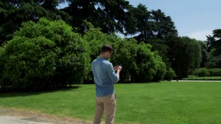 Man standing in the park and doing selfie on smartphone, steadycam shot