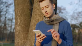 Man standing in the park and looks unhappy while talking on cellphone, steadycam