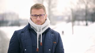 Man standing in the park at winter and doing serious look to the camera