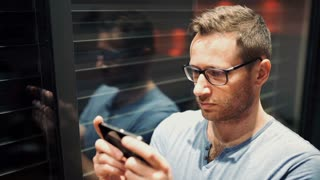 Man standing next to the window and texting on smartphone