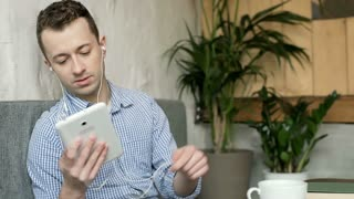 Man stops listening music on tablet and relaxing in the cafe