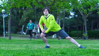Man stretching legs before jogging, steadycam shot, slow motion shot
