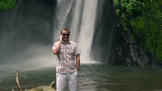 Man talking on cellphone next to the waterfall, slow motion shot at 240fps