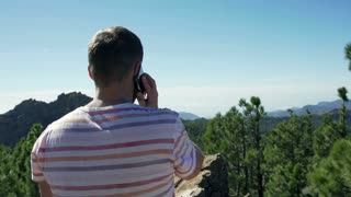 Man talking on cellphone while standing in the mountains and looking on beautifu
