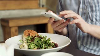 Man texting messages on smartphone during his lunch in the cafe