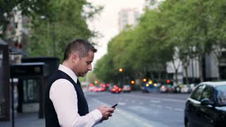 Man texting on smartphone and crossing street, steadycam shot