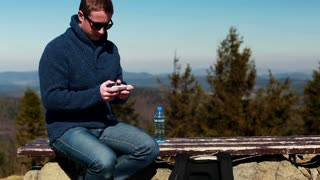 man texting on the cellphone and sitting on a bench in the mountainous area