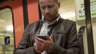 Man tweeting on the phone while traveling by metro, steadycam shot