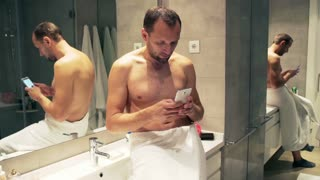 Man typing message on cellphone in the bathroom after shower