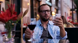 Man using a smartphone and drinking alcohol in a restaurant