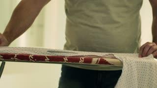 Man using iron to ironing his shirt at home