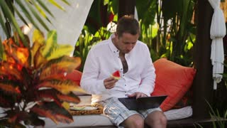 Man using laptop and eating watermelon in exotic garden
