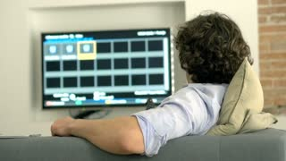 Man using remote control and browsing internet on tablet