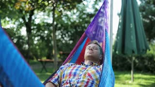 man waking up in the hammock after the short nap
