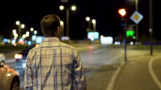 Man walking at night in the city, steadycam shot