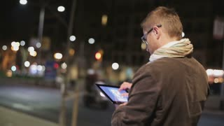 Man walking down the street at night and using tablet, steadycam shot