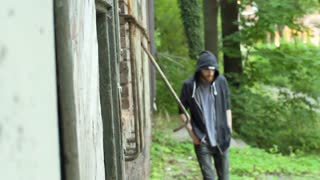 Man walking in abandoned, dark building and wearing hood, steadycam shot