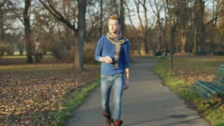 Man walking in the autumnal park and answers cellphone, steadycam shot