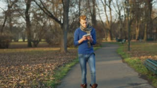 Man walking in the autumnal park and browsing internet on tablet, steadycam shot