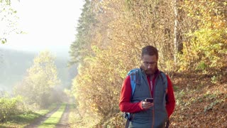 Man walking on autumnal pathway and browsing internet on smartphone, steadycam s