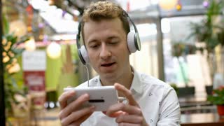 Man wearing headphones and watching something funny on smartphone