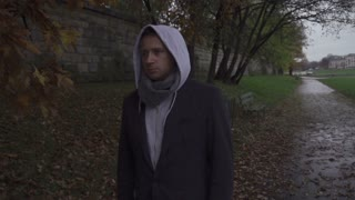 Man with hood walking on pathway, steadycam shot, slow motion shot at 240fps