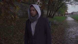 Man with hood walking on pathway, steadycam shot, slow motion shot