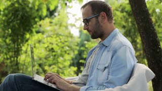 man working on a laptop and sitting in the garden