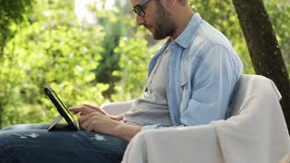 man working on his tablet in the garden