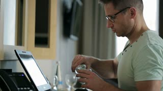 Man working on laptop and drinking water