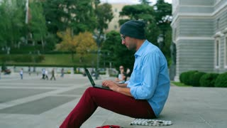 Man working on laptop and sitting on public square