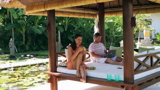 Man working on laptop and woman eating banana in exotic garden