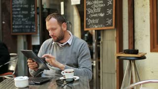 man working on tablet and drinking coffee outside the cafe