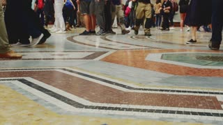 Masses of people walking on marble floor