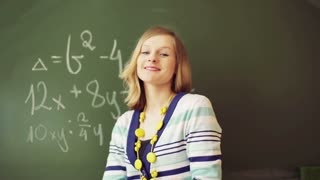 Math teacher holding chalk and smiling to the camera