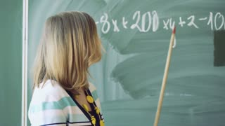 Math teacher standing next to the board and having a lecture, steadycam shot