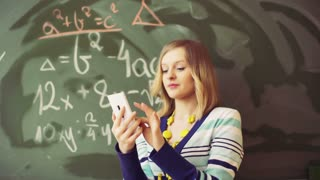 Math teacher texting on smartphone and smiling to the camera