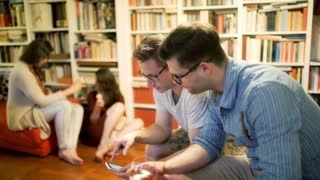 Men browsing internet on smartphone at the party