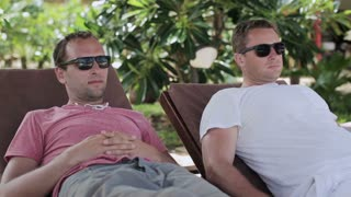 Men chilling on sunbeds, steadycam shot