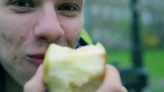 Men eating apple and smiling to the camera